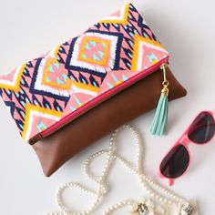 This zippered fold over clutch features a tan faux leather on one side and a coral pink, mint, and navy tribal Ikat fabric on the other side. The