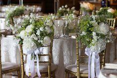 Brides: A Destination Wedding at Downton Abbey - arrangements of white flowers decorate wedding chairs