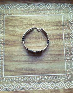 Bracelet femme fait main, composé de perles en cristaux noirs, et de tubes en argent ciselé,de perles en métaux (sans nickel) monté sur fil à mémoire de forme. Le bracelet mesure 6.5cm de diamètre. Envoyé avec un emballage pret à offrir. FRAIS DE PORT OFFERT !!!!!! (Seulement pour la