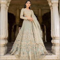 Light Blue Gold Embroidered Omorose Pakistani Bridal Lehenga <br> If you are looking for some unique ethnic wear this festive season, check out some gorgeous lehengas, kurtas, and more by Pakistani Bridal Designers. Pakistani Bridal Lehenga, Pakistani Wedding Dresses, Modest Wedding Dresses, Indian Dresses, Saree Wedding, Bridal Dresses, Gold Lehenga, Wedding Dress With Pockets, Lace Dress With Sleeves
