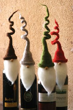"Wine toppers make the gift of wine incredibly special, and these charming santas with whimsical, curly hats will be an instant hit at any holiday party this season! Set of four. One of each color. 11""t"