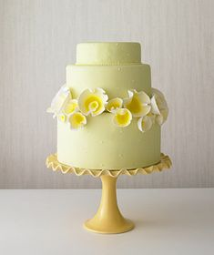 Yellow sugar tulips create a graphic ring around a three-tier cake, by The Cake Girls via Real Simple
