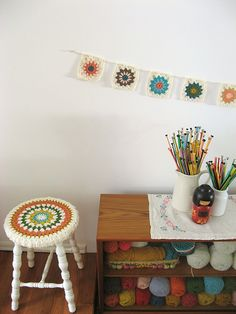 perfection... stool cover, bunting... needles... yarn... love this little corner!