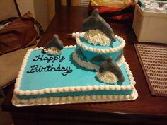 Dolphin cake... something along these lines?? USE DOLPHIN CANDY MOLDS - LIKE SMALL ROUND VAKE ON TOP OF SHEET CAKE!