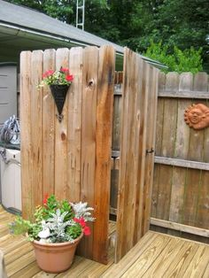 A few extra feet of fencing and a water source is all it took to create this casual outdoor shower. A sliding wooden door provides maximum privacy.