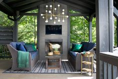 The fireplace in this Georgia log cabin was covered in inexpensive porcelain tile. The brass chandelier finishes the space with a little sparkle.   - HouseBeautiful.com