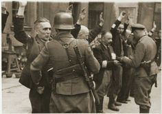 SS troops and officers search the Jewish department heads of the Brauer armaments factory during the suppression of the Warsaw Ghetto Uprising.  Photo credit: Poland National Archives.