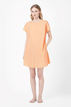 Made from crisp papery cotton with a lightweight quality, this simple tunic dress has a low back with fabric tie fastening. A comfortable, oversized style that can be worn as a dress or cover-up, it has short capped sleeves, side seam pockets and a wide round neckline.