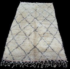 Beni Ourain rug (picture is an original). Check out blogger's DIY version, created using affordable ivory rug from a superstore and embroidery thread.