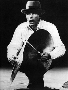 """Joseph Beuys (1921 – 1986) was a German Fluxus, Happening and performance artist as well as a sculptor, installation artist, graphic artist, art theorist and pedagogue of art.  His extensive work is grounded in concepts of humanism, social philosophy and anthroposophy; it culminates in his """"extended definition of art"""" and the idea of social sculpture as a gesamtkunstwerk, for which he claimed a creative, participatory role in shaping society and politics."""
