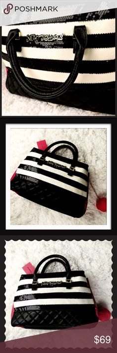 """Betsey Johnson Sequin Black White Stripe Satchel New with tags attached and no defects.  Sequin embellishment on black and white stripes on front and back of Satchel. 5"""" drop top handles. Red pom 2.5"""" diameter  keychain removable. Size approx 16"""" L x 14"""" H x 4"""" W (medium size).  Red accent faux leather on sides and black Quilted faux leather on bottom and handles.  Magnetic close on top and 2 compartments with interior zip pocket and 2 open pockets. Center compartment with Zip closure…"""