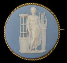 1870s Antique Round Wedgwood Cameo Pin/Brooch in a Classic Brass Setting. The image is of Apollo who was the great Olympian oracle on healing, plagues and disease, music, song and poetry, archery, and protection of the young. Depicted as a handsome, beardless youth with attributes including a wreath and branch of laurels, bow and quiver, raven, and lyre. This is 50mm in diameter with a C clasp in the rear.  The cameo is stamped WEDGWOOD on the back.