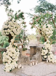 White hydrangea wedding arch: Photography: Gianny Campos Photography - www.giannycampos.com Read More on SMP: http://www.stylemepretty.com/2017/04/12/show-stopping-fashion-tucked-inside-a-glamorous-wedding-by-the-sea/