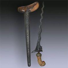 "Keris Naga Kikik - Jogyakarta  17th century 13 ""Luk"" Keris dapur Naga Kikik tangguh Mataram Sultan Agung (1613 to 1646), warangka gayaman Jogyakarta, central Java, hilt carved in an elephant ivory, sheath made from Timoho wood.  The base of the blade represente a dog, similar in shape to the ""Singa Barong"" which represente a lion. The pamor is ""Wos Wutah"". Swords And Daggers, Knives And Swords, Barong, Dagger Knife, Arm Armor, Cold Steel, Tribal Art, 17th Century, Weapons"
