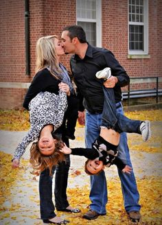 Parents Kissing While Holding Children Upside Down