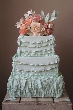 Mint green feathers wedding cake with gold gilding and peach-colored gumpaste flowers by Megan Joy Cakes.