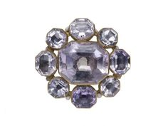 An openwork octofoil of gold and enamel with nine foiled amethysts in octagonal bezels: eight surrounding a larger central stone. It is enamelled on the reverse in black and white. The function of the jewel remains uncertain since there are no loops or clasps for attachment. Part of the Cheapside Hoard, 16th century-early 17th century.