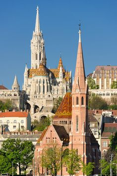 Churches in Budapest, Hungary: Calvinist Church (in the foreground) and Matthias Church (behind). On the left you can see one of the towers of Fisherman's bastion. on the right side on the hill is the Hilton Hotel. Available as poster, framed fine art print or canvas print. (c) Matthias Hauser hauserfoto.com