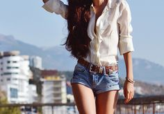 Nice white blouse with a leather belt and denim shorts!