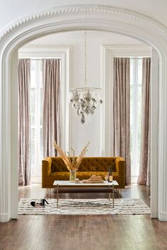 Velvet love seat sofa in a living room with chandelier and French-inspired architecture