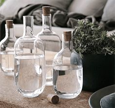 Nahaufnahme mehrerer SINNERLIG Flaschen aus Klarglas in verschiedenen Größen, alle mit einem Korken versehen.