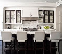 Jennifer Worts Design.    Gorgeous kitchen design with white kitchen cabinets, marble tiles backsplash, glass pendants, espresso kitchen island, marble counter tops, chrome faucet and hardware and white leather stools.