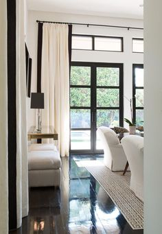 Living Room with black framed French doors and white slipcovered chairs