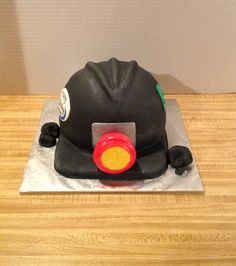 Coal Miner Hard Hat 8 inch diameter 1/2 Chocolate and 1/2 White cake. Iced with buttercream, covered with fondant. Accented with silver...