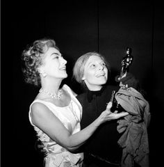 """Anne Bancroft, right, is presented the Oscar award from Joan Crawford in front of the audience at the Martin Beck Theater where Bancroft is starring in """"Mother Courage and Her Children,"""" in New York City on May 6, 1963.  Bancroft, who was unable to attend the Academy Awards ceremony, won the Best Actress award for her portrayal of Annie Sullivan in the film adaptation of the play """"The Miracle Worker.""""  (AP Photo)"""