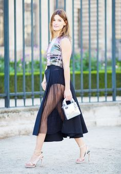Printed sleeveless top paired with a black skirt with sheer, pleated panel, and metallic mini bag