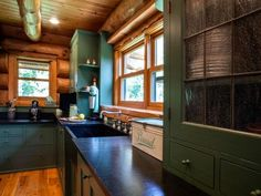 Painted cabinets with antique-looking glass add to the lodge look of this space by Tami Holsten of Bear Trap Design.