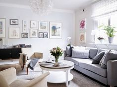 Gray sofa with framed artwork and round coffee table.