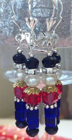 These adorable and Festive Nutcracker Christmas Earrings are made with Blue, Black and Red Cubed Glass Crystals. Silver toned Flower Bead Spacers, a small white Pearl and lovely Rhinestone Rondelles. These Earrings are suspended from Silver Shell Earring lever back plated brass ear wires. They are a perfect Christmas Gift for any fan of the Famous Nutcracker Musical. They are adorable, delicate and festive. Youll be sure to get many compliments on these lovely and unique Toy Soldier…