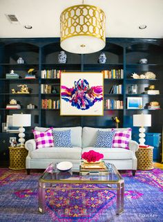 Add a unique twist to your interior design with this collection of colorful home decor ideas from the team at Me Craftsman. This home library pairs dark blue built-in bookshelves with modern wall art, neutral furniture, a purple aztec rug, and gold accents to create an eclectic style. Get even more design inspiration by clicking here.