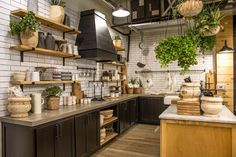 The biggest transformation we (Magnolia Silos) made was adding the kitchen area. First, we installed classic subway tile and black lower cabinets and concrete countertops. This gave a clean yet neutral foundation that will let each season's displays really stand out. ...