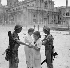 Italian nurses dress the minor wounds of two British soldiers in Catania, 5 August 1943.