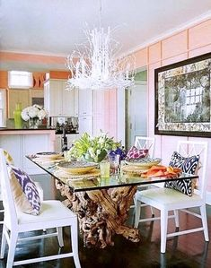 Love the twig chandelier, driftwood table base, and collection of ikat pillows on the chairs.