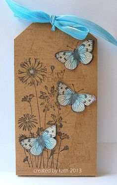sweet handmade tag ... kraft paper ... three die cut butterflies in white and blue ... stamped meadow flowers left as line drawing ..