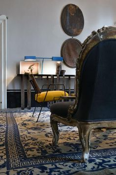 Mix of modern and antique vintage furnishings in apartment in Italy with blue rug