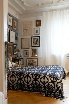 Barbara Gehri's lovely Zurich bedroom - the accent wall at the head of the bed is painted in a warm gray while the corner next to the bed features a gallery wall. A handmade applique black and white bedspread adds to the casual, elegant, bohemian look while white curtains add balance.
