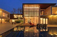 Situada entre três grandes árvores, esta casa é formada por dois blocos retangulares conectados por uma estrutura estreita e transparente