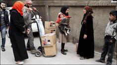 Varias personas guardan cola para recibir ayuda humanitaria iraní en el barrio de Al Zahira en Damasco (Siria). ©Youssef Badawi-efe