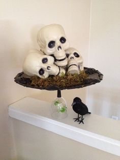 Halloween dollar tree diy centerpiece. 3 plastic skulls, plastic party tray, upside down wine glass for stand, and a little crow. $7 for supplies.