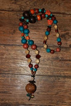 Necklace with beige, brown, turquoise & orange wood beads, brown glass beads, orange buddha's, turquoise stone beads, orange & white skulls, brown faceted glass beads & charm beads. 30 €