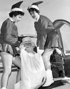 "In December 1958, the second annual ""Operation Santa Claus"" of the Nebraska Civil Air Patrol was ready to take flight. Before the flight, Santa (Maj. Harry A. Wakefield, Air Force Liaison Officer) was handed a bag of candy by two sprightly elves, Michele Jones, left, and Pat Limas. Santa was to use the candy to barter for old toys with children in several small Nebraska towns. The toys were to be used for charity. THE WORLD-HERALD"