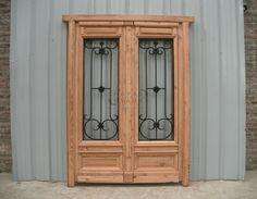 Puerta de frente de pinotea con rejas de hierro forjado