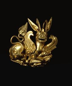 OXUS TREASURE - Gold ornament, possibly an aigrette, representing on the front a recumbent lion-griffin with bent legs.  Achaemenid 5thC BC-4thC BC.  © The Trustees of the British Museum | The Oxus treasure is a collection of about 180 surviving pieces of metalwork in gold and silver, the majority rather small, plus perhaps about 200 coins, from the Achaemenid Persian period which were found by the Oxus river about 1877-1880.