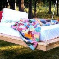 Bed van pallets met matras in de tuin, hangend aan een boomtak.