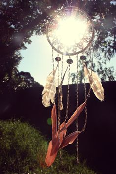 Garden dream catcher. This is great inspiration to do wire wrapping in the center with sea glass and beads.  Maybe hang chimes instead of feathers