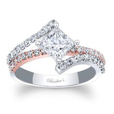 This two tone rose and white gold diamond engagement ring features a prong set princess cut diamond center. The white gold ridges of the split shank are adorned with shared prong set diamonds. A rose gold diamond bridge runs though the center